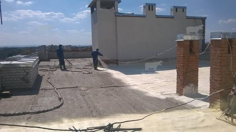 Процесс напыления пенополиуретана на крышу многоэтажного дома